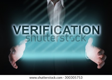 "Glowing text ""verification"" in the hands of a businessman. Business concept - stock photo"