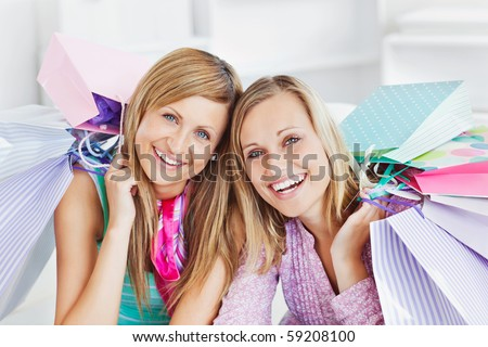 Glowing two women holding shopping bags smiling at the camera at home - stock photo