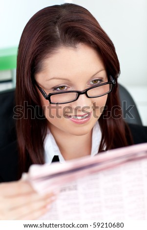 Glowing young businesswoman reading a newspaper in her office - stock photo