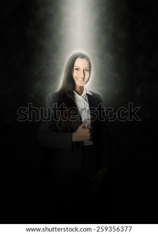 Glowing Young Businesswoman Showing Thumbs up Hand Sign with a Smile on an Abstract Black Background. - stock photo