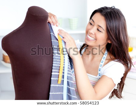 Glowing young woman working with clothes in the kitchen at home - stock photo