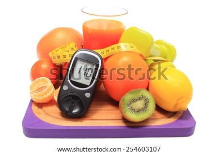 Glucometer. fresh fruits, dumbbells for using in fitness, tape measure and glass of juice, concept for diabetes, slimming, healthy nutrition and strengthening immunity - stock photo
