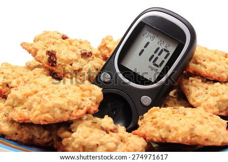 Glucose meter and oatmeal cookies lying on colorful plate, concept for diabetes and healthy nutrition. Isolated on white background - stock photo