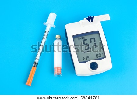 Glucose meter, Insulin and syringe on a blue background - stock photo