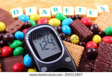 Glucose meter with word diabetes, heap of candies, cookies and brown cane sugar, too many sweets, unhealthy food, concept of diabetes and reduction of eating sweets - stock photo