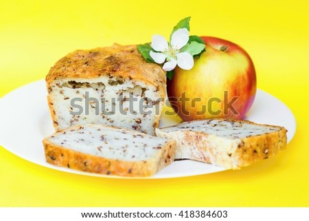 Gluten free bread with many flax seeds, apple and apple flower, isolated on yellow background, closeup - stock photo