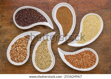 gluten free grain abstract - top view of teardrop shaped bowls with quinoa, teff, millet, rice, sorghum and buckwheat grains against grunge wood - stock photo