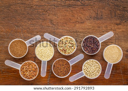 gluten free grains (quinoa, brown rice, kaniwa, amaranth, sorghum, millet, buckwheat, teff) - a set of measuring scoops on a rustic wood with a copy space - stock photo