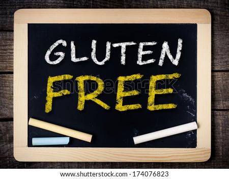 Gluten Free handwritten with white chalk on a blackboard on wood background  - stock photo