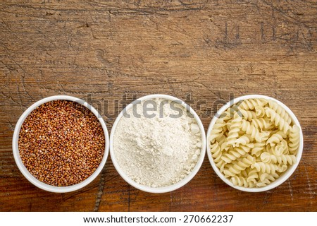 gluten free quinoa grain, flour and pasta - top view of small ceramic bowls against rustic wood with a copy space - stock photo