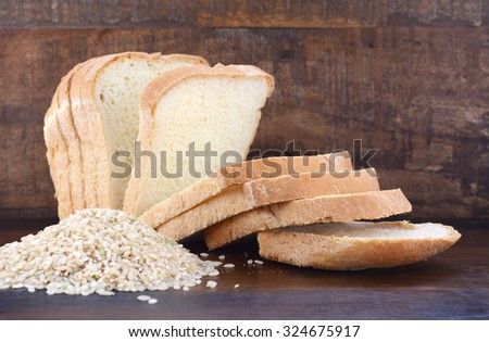 Gluten free rice sliced sour dough bread with raw brown rice on dark wood table background.  - stock photo