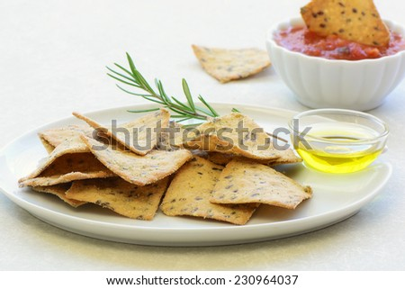Gluten free rosemary and olive oil crackers on white plate in horizontal format - stock photo