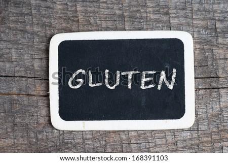 Gluten handwritten with white chalk on a blackboard on wood background - stock photo