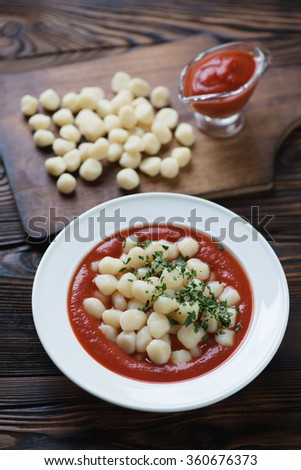Gnocchi served with tomato sauce on a rustic wooden background - stock photo