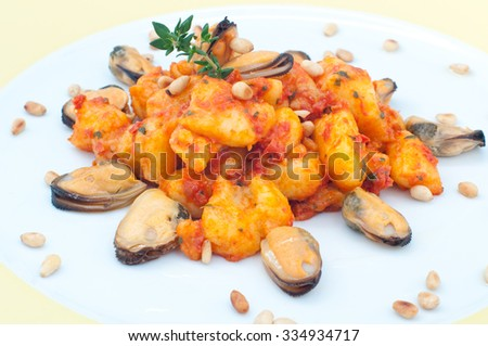 Gnocchi with tomato sauce with mussels, italy - stock photo