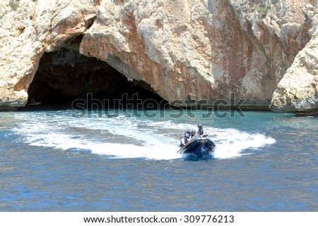 Go fast coastguard boat watching a cavern in the cliffs of Moraira - stock photo