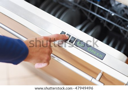 Go Green concept. Close up of woman using dishwasher in energy saver mode. Horizontal shape - stock photo