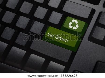 Go green key with wind turbine icon on keyboard - stock photo