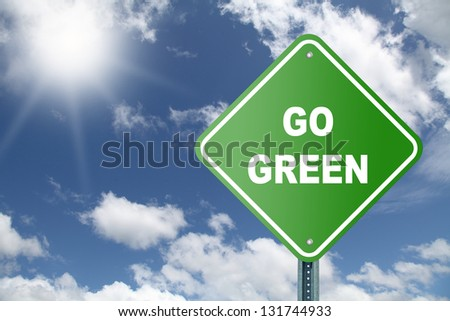 Go Green road sign on beautiful sky background - stock photo