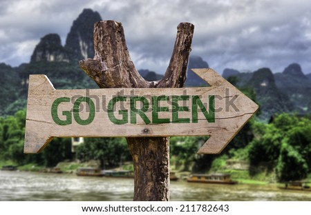 Go Green wooden sign with a forest background  - stock photo
