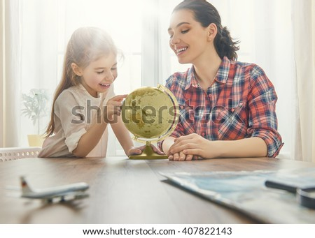 Go on an adventure! Happy family preparing for the journey. Mom, dad and daughter study the globe and choose a route of travel. - stock photo
