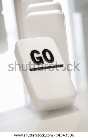 Go text on a domino that is about to collapse a set - stock photo