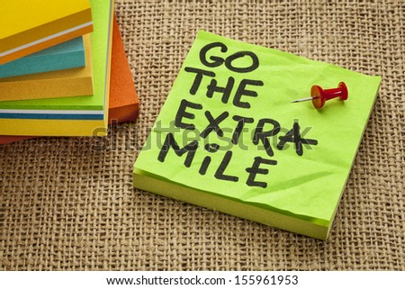 go the extra mile  - motivational reminder or procrastination concept  - handwriting on sticky note - handwriting on sticky note - stock photo