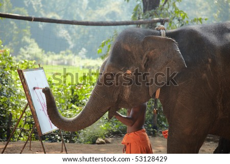 GOA, INDIA - DECEMBER 15: Elephant drawing a picture on elephants show on December 15, 2009 in Goa, India. Elephants show is a main attraction for tourists in this region. - stock photo
