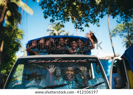 Goa, INDIA - October 25: Unidentified school children in uniform going home after classes at primary school by school bus on october 25, 2014. India, Goa - stock photo
