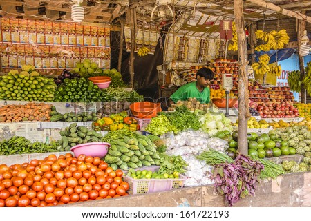 GOA, INDIA - SEPTEMBER 26, 2013: Unknown seller of fruits and vegetables in a small market in Vagator, Goa. Vegetables, fruits and seafood is one of the main part of Indian peoples ration. - stock photo
