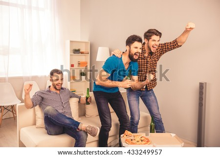 Goal!  happy joyful men sitting on sofa and watching sport tv with beer and pizza - stock photo