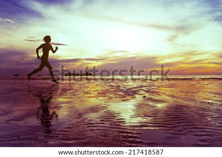 goal, silhouette of barefoot woman running on the beach - stock photo
