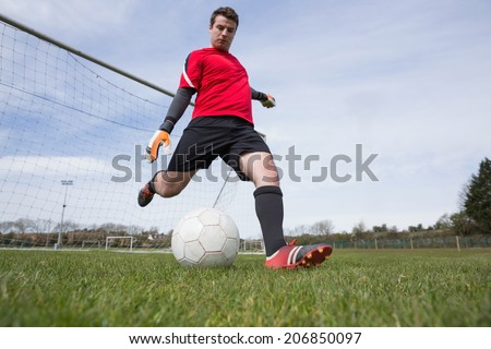 Goalkeeper in red kicking ball away from goal on a clear day - stock photo