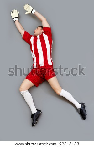 Goalkeeper jumping high to catch the ball - stock photo