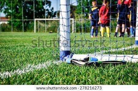 Goalpost detail: children waiting for the football match to start  - stock photo