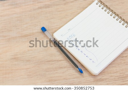 Goals for 2016 - checklist on notepad with pen on wooden background - stock photo