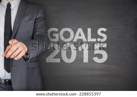 Goals 2015 on blackboard with businessman hand pointing - stock photo