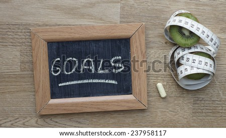 Goals written on a chalkboard next to a kiwi an inches - stock photo