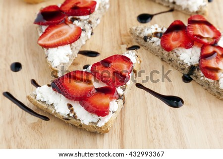 Goat's cheese and strawberry bruschetta with drizzle of balsamic cream. - stock photo