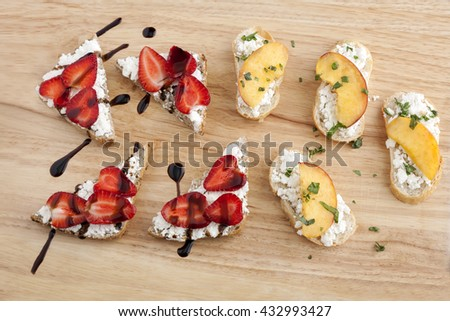 Goat's cheese, peach and strawberry bruschetta healthy finger food. - stock photo