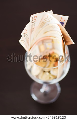 Goblet for wine full of banknotes and coins - stock photo