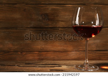 Goblet of red wine on wooden table on wooden wall background - stock photo