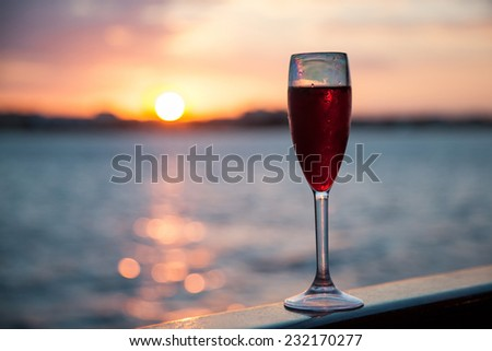Goblet with red wine on sea background - stock photo