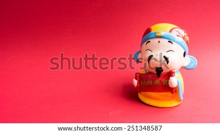 God of prosperity doll or deity chinese figurine holding message 'Prosperity' and 'Money and Fortunes Come'. Concept for Chinese Lunar New Year greetings announcement.  Slightly defocused. Copy space. - stock photo