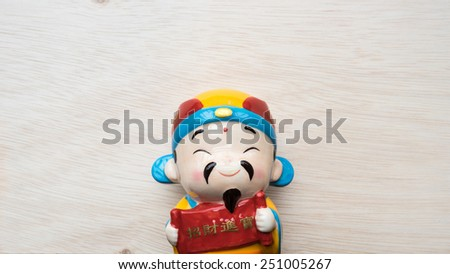 God of prosperity doll or Deity figurine holding a message 'Prosperity' and 'Money and Fortunes Come'. Concept of Chinese Lunar New Year. Slightly defocused and close-up shot. Copy space. - stock photo