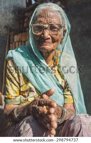 GODWAR REGION, INDIA - 13 FEBRUARY 2015: Elderly Indian woman in sari with covered head and repaired glasses sits in doorway of home. Post-processed with grain, texture and colour effect. - stock photo