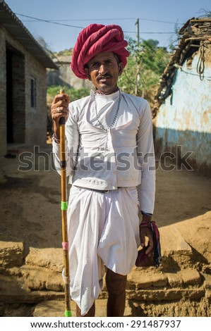 GODWAR REGION, INDIA - 13 FEBRUARY 2015: Rabari tribesman stands in courtyard in traditional clothes and holds herding stick. Rabari or Rewari are an Indian community in the state of Gujarat. - stock photo