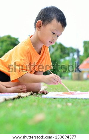 Going back to school :Cloe up Boy drawing and painting over green grass background - stock photo