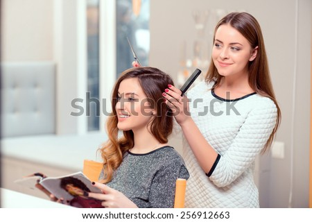 Going for a change of style. Young beautiful woman discussing hairstyling with her hairdresser holding a comb and scissors while sitting in the hairdressing salon - stock photo