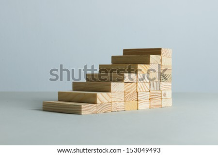Going up concept using stairway of wood blocks - stock photo